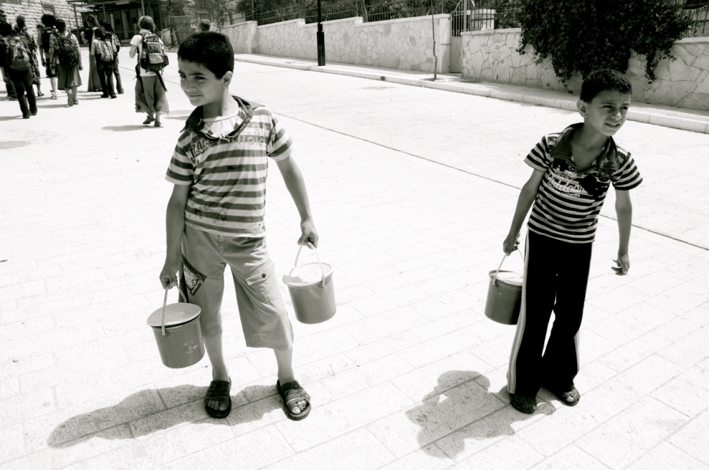 Boys carrying soup